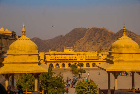 amber light: Amber Fort illuminated by warm light of the rising sun and reflected in the lake. Famous Rajasthan landmark located nearby Jaipur city in north-western India. Stock Photo