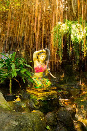 A small statue on the background of water and rocks at the temple. Thailand. Bangkok. Stock Photo