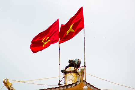 Close-up. Development of the flag. Water tower in Phan Thiet.Vietnam.Two red flag: the hammer and the young star