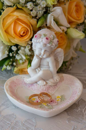 angel roses: Two beautiful gold wedding rings lie on a platter in a rose shape with the angel sculpture near the brides bouquet of orange roses and white flowers.
