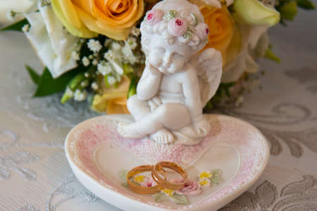 Two beautiful gold wedding rings lie on a platter in a rose shape with the angel sculpture near the brides bouquet of orange roses and white flowers.