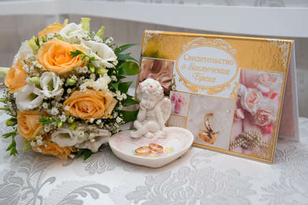angel roses: Two beautiful gold wedding rings lie on a platter in a rose shape with the angel sculpture near the brides bouquet of orange roses and white flowers. The certificate of marriage.