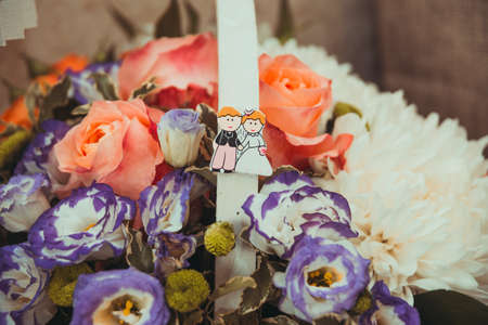 adorned: A beautiful basket of flowers from roses, which adorned the handle with a picture of the bride and groom