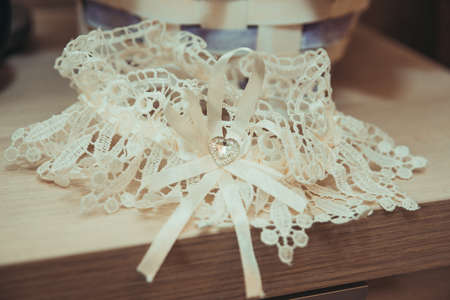 Beautiful lace garter for the bride is on the table