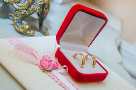 Two beautiful wedding gold rings with diamonds are in a red box.