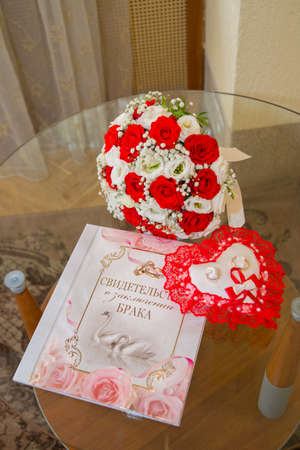 Two beautiful gold wedding rings lie on a cushion in the shape of a heart with a red lace around the brides bouquet of red and white roses. The certificate of marriage with a pattern of swans and rings. Stock Photo