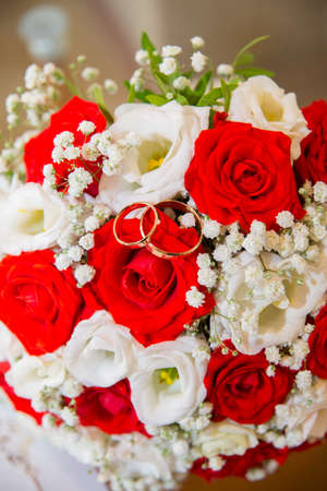 Two beautiful gold wedding rings lie on a bouquet of red and white roses.
