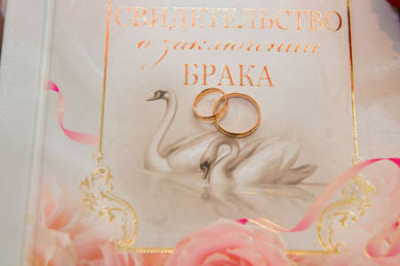 reflection of life: Two beautiful gold wedding rings lie on the background of the certificate of marriage with a pattern of swans and rings. Stock Photo