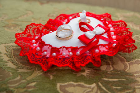 Two beautiful gold wedding rings lie on a cushion in the shape of a heart with a red lace