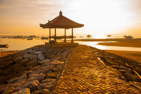 road of stone leads to a Pavilion to rest. Beautiful morning at Karang beach, Sanur in Bali, Indonesia. Dawn