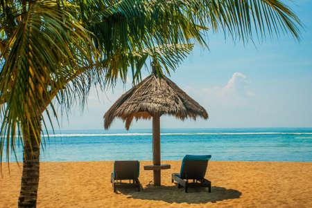Benoa sand beach view. Bali, Indonesia, Tanjung Benoa. Nusa Dua. Sun loungers and parasols on the beach.