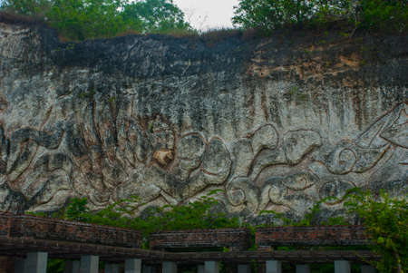 Wall of rock on which there is a relief image. Public Area. Garuda Wisnu Kencana Cultural Park. Bali. Indonesia. GWK.