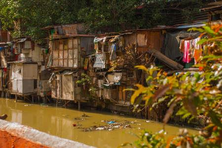 third world: Many shacks located at slum region in Manila, Philippines. House near the pond with garbage