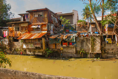 Many shacks located at slum region in Manila, Philippines. House near the pond with garbage
