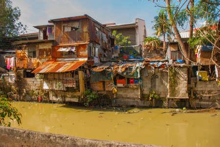 Vele hutten gelegen in Slum regio in Manilla, Filipijnen. Huis dichtbij de vijver met vuilnisbak