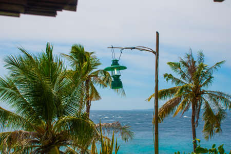 Apo island,Philippines, view on island beach line. Palm trees, lantern, sea and boats. The tropical landscape, view from the top.
