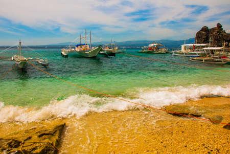 Apo island,Philippines, view on island beach line: rocks, sea and boats Stok Fotoğraf