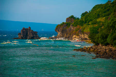 Apo island,Philippines, view on island beach line: rocks, sea and boats, the view from the top.