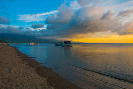 The volcanic sandy beach at sunset. The ships at sea. Pandan, Panay island, Philippines Stock Photo