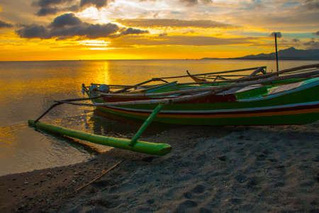 Beautiful sunset on the beach. Local boats standing on the shore. Pandan, Panay island, Philippines
