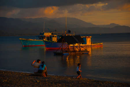 Sunset on the beach. People sit on the beach and watch the ships and the sea. Pandan, Panay island, Philippines