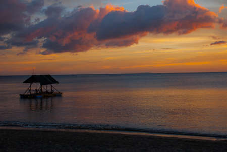 Beautiful sunset on the beach. Silhouettes of pavilions. Pandan, Panay island, Philippines Stock Photo