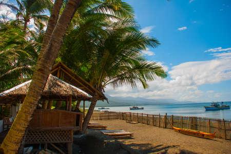 Zonnebanken en palmbomen op het strand tegen de zee. Pandan, Panay eiland, Filipijnen. Stockfoto