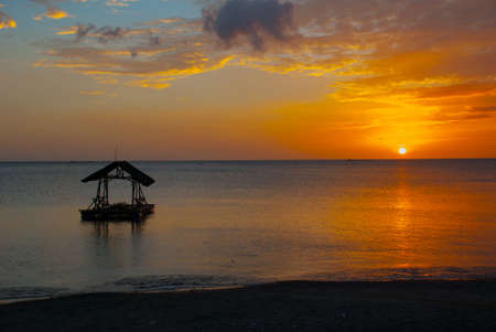 Beautiful sunset on the beach. The silhouette of the gazebo. Pandan, Panay island, Philippines