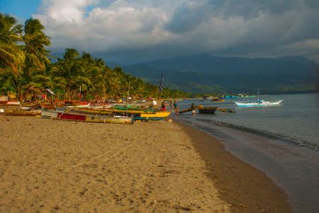 Landscape with clouds, mountains in cloudy weather. The volcanic sandy beach with boats. Pandan, Panay island, Philippines.