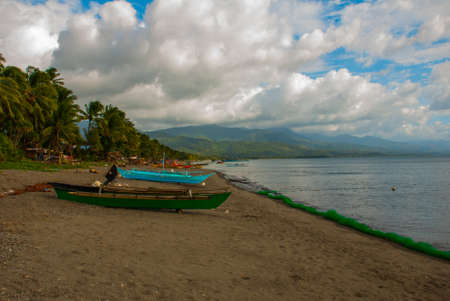 Landscape sky with clouds, mountains in cloudy weather. The volcanic sandy beach with boats. Pandan, Panay island, Philippines.