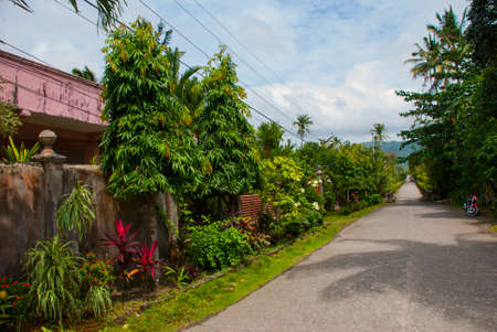 Rural road with houses in the Philippines. Pandan, Panay island Stock Photo