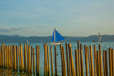 Landscape with sailing boats and mountains in background. Boracay island, Philippines