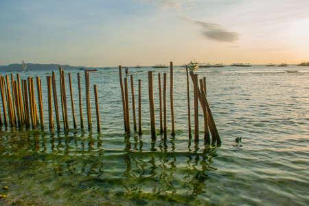 Paisaje de mar con una valla en el agua con montañas en el fondo. Isla de Boracay, Filipinas