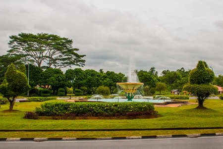 A small fountain in a Park with trees trimmed in the shape of cats. Kuching, Borneo, Sarawak, Malaysia Stock Photo