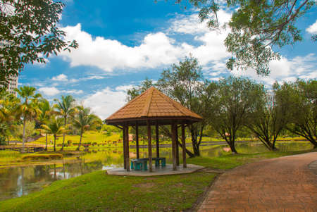 The gazebo by the waterfall. Beautiful Landscape in a park with trees on a sunny day. Kuching. Sarawak. Borneo. Malaysia Stock Photo