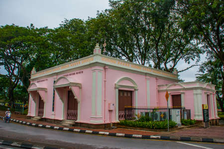 A pink beautiful building of the Chinese historical Museum with trees in the background. Kuching. Sarawak. Borneo. Malaysia Stock Photo