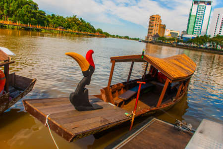 Landscape view of the city and Sarawak river. Local traditional boat for tourists. Kuching, Borneo, Sarawak, Malaysia