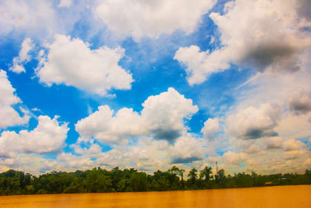 Landscape with yellow river and blue sky with clouds. Sarawak, Malaysia, Borneo