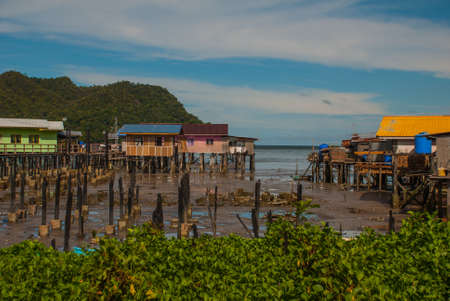Traditional houses on stilts over the water. Sandakan city, Borneo, Sabah, Malaysia Stock Photo