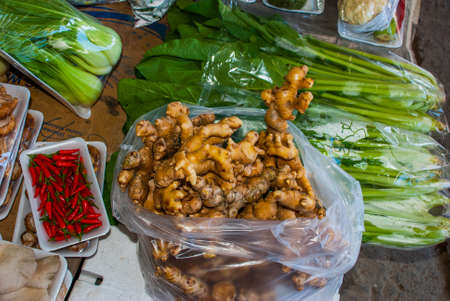 Ginger, pepper, onions. The traditional Asian market with food. Sale a variety of vegetables lying on the counter. Malaysia Stock Photo