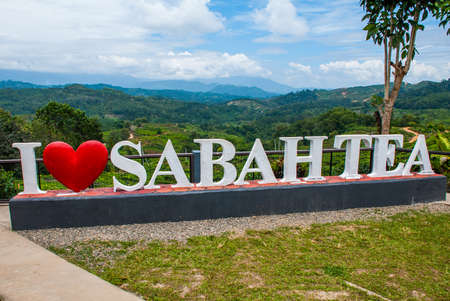Huge white lettering I love Sabah tea. The mountains on the horizon. Borneo island, Malaysia