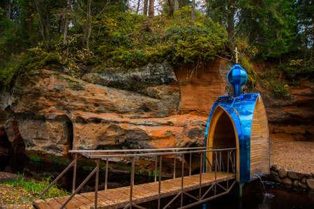 pila bautismal: Fuente bautismal ortodoxa hermosa en un resorte y rocas en el bosque del otoño. Rusia. Óblast de Leningrado. Foto de archivo