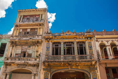 Traditional buildings in classic style with colorful facades on the background of blue sky with clouds. Havana, capital of Cuba