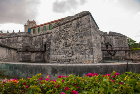 Castillo de la Real Fuerza on blue sky background with clouds. The old fortress Castle of the Royal Force and flower bed with red colors. Havana, Cuba.