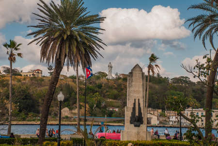 Cuba flag and statue of Jesus Christ on a hill overlooking the port and the bay of Havana, Cuba. Stock Photo