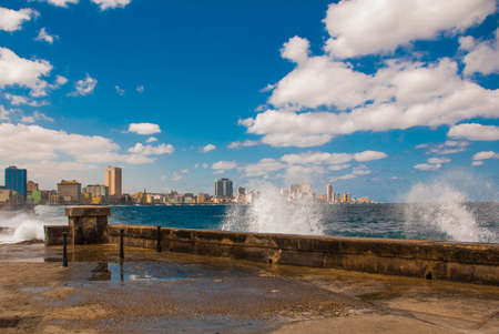 Splashes of waves. View from the Malecon promenade to the city. Cuba. Havana Stock Photo