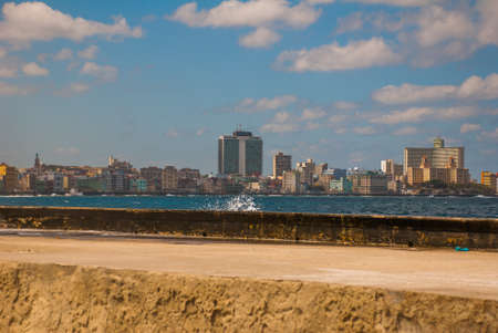 Splashes of waves .View from the Malecon promenade to the city. Cuba. Havana.