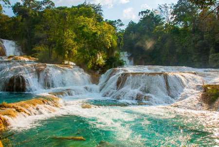 Agua Azul, Chiapas, Palenque, Mexico. View of the amazing waterfall with turquoise pool surrounded by green trees. Wonder of nature.