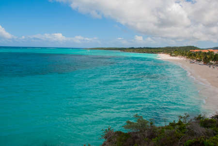 Playa Esmeralda in Holguin, Cuba. The view from the top of the beach. Beautiful Caribbean sea turquoise and blue sky with clouds. Banco de Imagens - 99616388