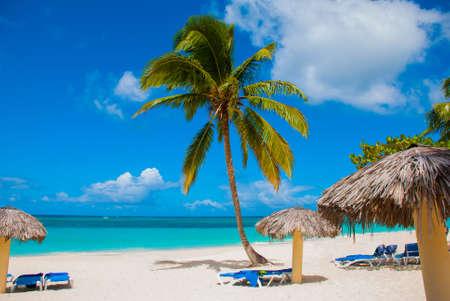 Holguin, Cuba, Playa Esmeralda. Beautiful Caribbean sea turquoise blue color and palm trees on the beach. Sun loungers and umbrellas for tourists. Stock Photo